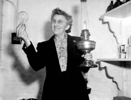 Fannie Salter holds an electric light bulb the incandescent oil lamp that the bulb replaced. Photo courtesy of the U.S. Coast Guard